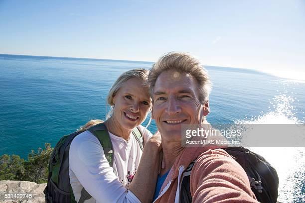 Hiking couple take selfie high above sea