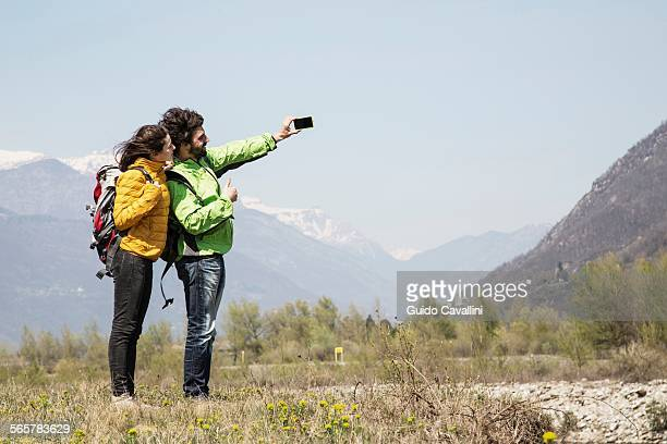 Hiking couple taking smartphone selfie, Vogogna, Verbania, Piemonte, Italy