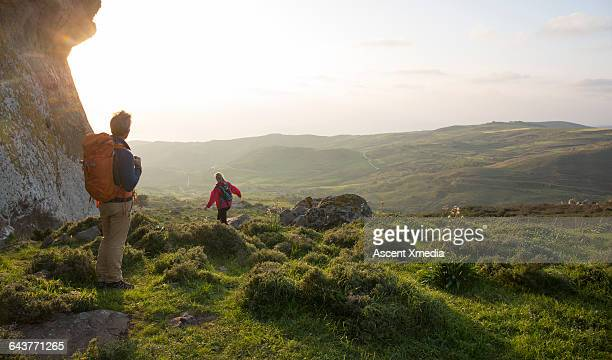 Hiking couple walk across meadow towards hills