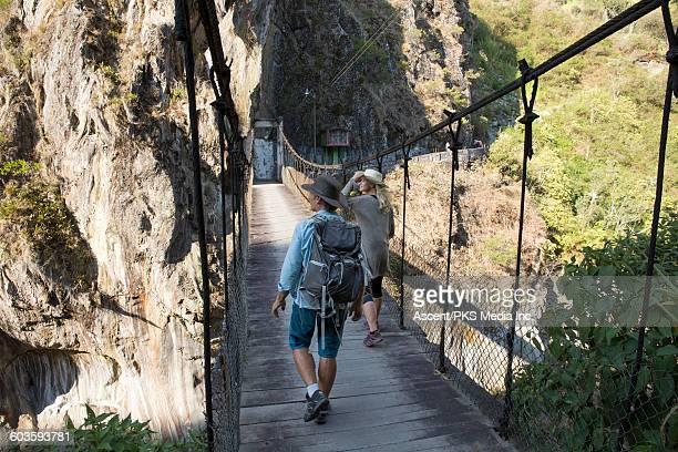 hiking couple walk across suspension bridge - hängebrücke stock-fotos und bilder