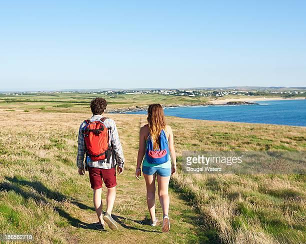 Hiking couple walking along path on UK coastline.