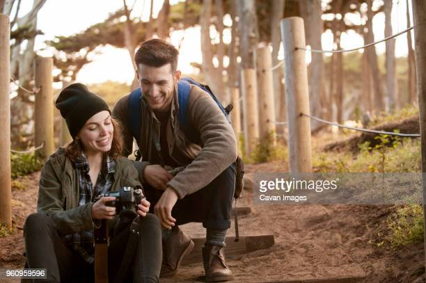 Hiking couple watching photographs on camera at forest