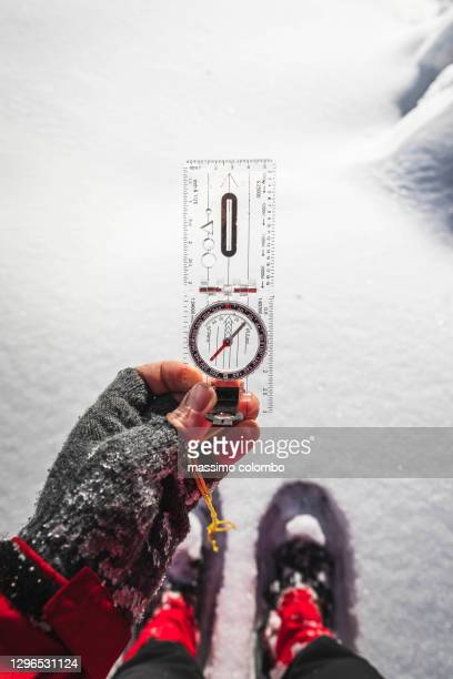 hiking, detail of hand with compass for orientation in the mountains - geografia fisica foto e immagini stock