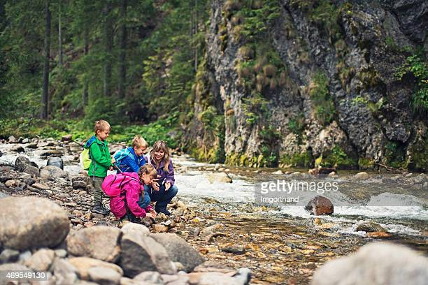 Hiking family at the bank of the beautiful moutain river.