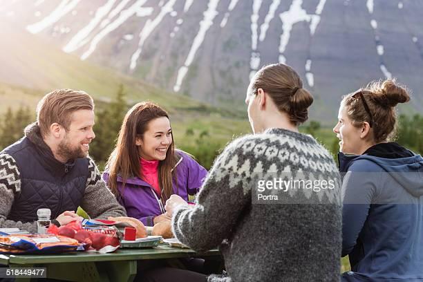 Hiking friends having food at picnic table