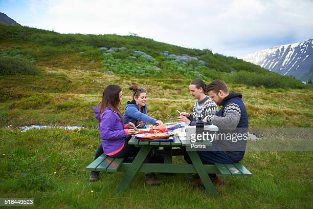 Hiking friends having food at table on mountain