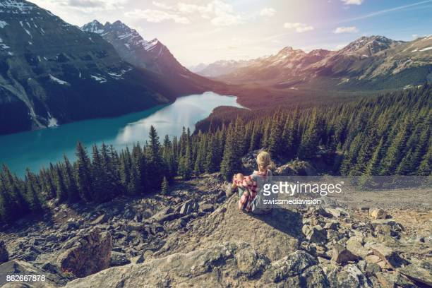 Hiking girl reaching mountain top, looks at view