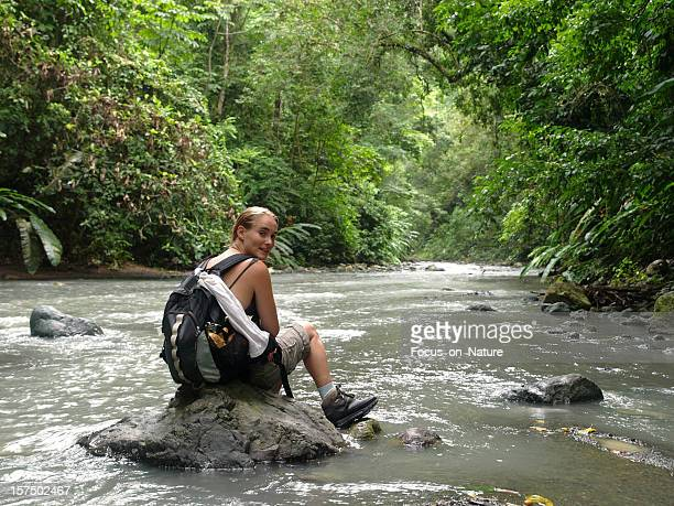 Hiking girl resting on a rock in the middle of a river