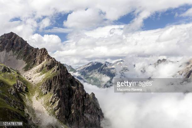 hiking in maira valley - over the clouds. - valle foto e immagini stock