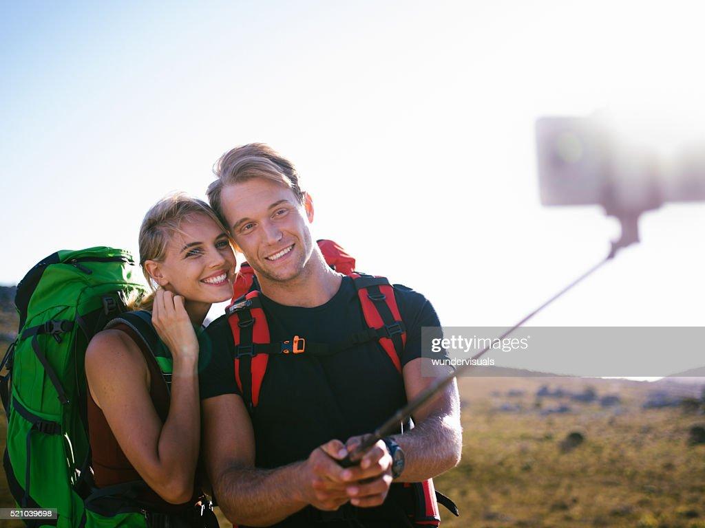 Randonnée homme et femme prenant selfie avec monopode dans la nature : Photo