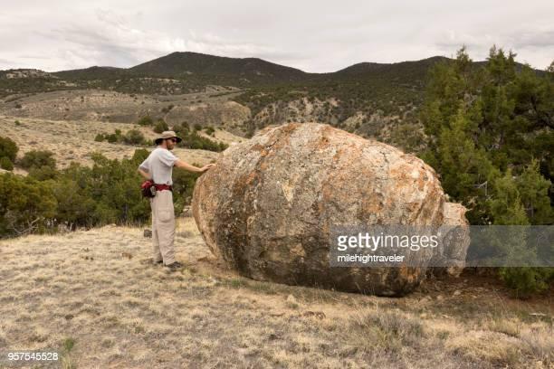 Hiking man explores ancient huge Ducey Stromatolite limestone fossil northwest Colorado