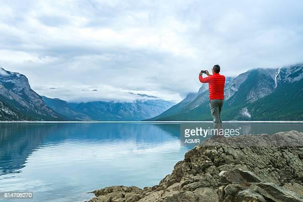 homem de caminhada usar telefone inteligente tirando foto - largo descrição geral - fotografias e filmes do acervo