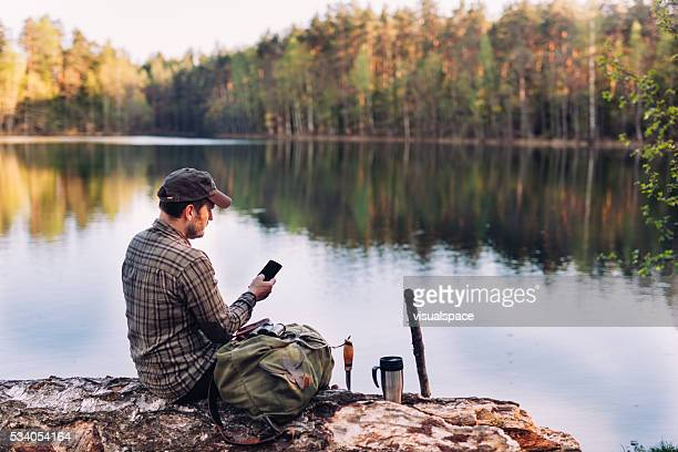 Hiking Man Using Smartphone By The Lake