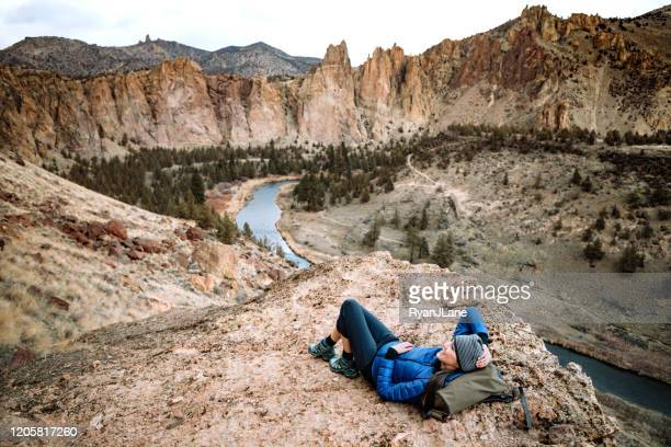 hiking mature adult woman stops to look at view - smith rock state park stock pictures, royalty-free photos & images