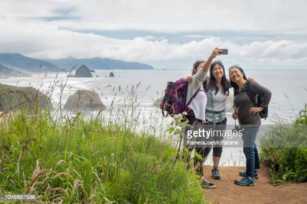 hiking mother, daughters taking selfie from lookout with beach background - oregon coast stock pictures, royalty-free photos & images