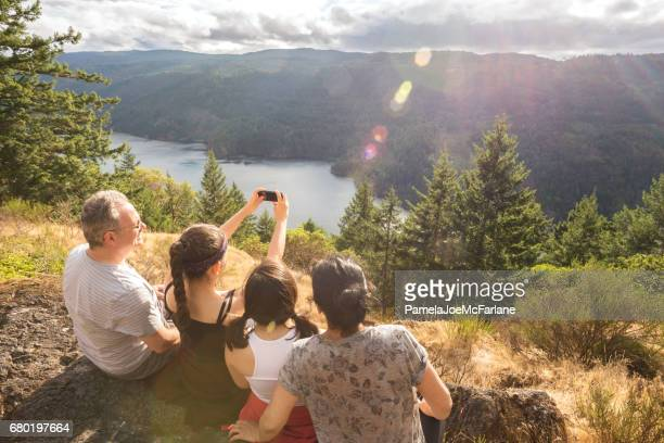 hiking, multi-ethnic family taking selfie on mountain summit with cellphone - british columbia stock pictures, royalty-free photos & images