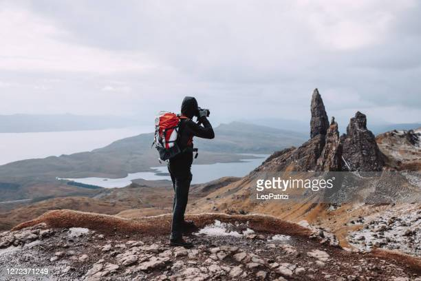 hiking on a solo adventure in mountain and photographing the magic of old man of storr - photographer stock pictures, royalty-free photos & images