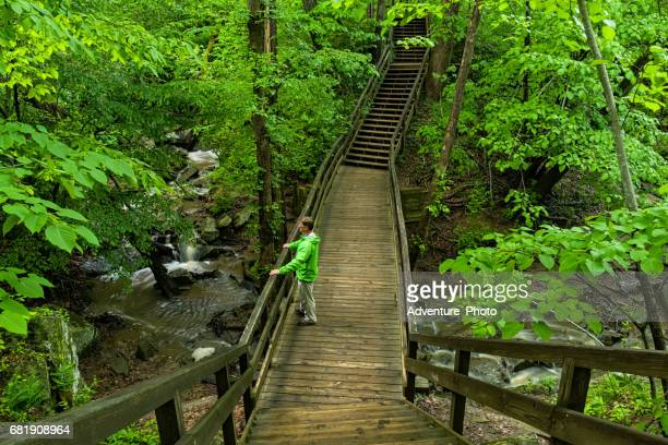 hiking over creek on bridge in great falls virginia - mclean virginia stock pictures, royalty-free photos & images