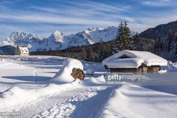 hiking path, snow covered log cabin and karwendel mountain range - krün stock pictures, royalty-free photos & images