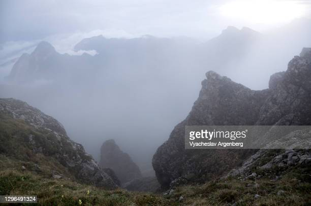 hiking the slopes of asbestnaya mount in heavy fog and clouds, adygea, caucasus mountains - argenberg stock pictures, royalty-free photos & images
