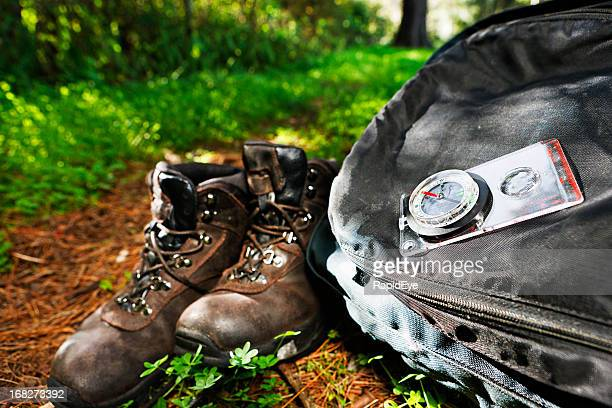Hiking theme: boots, backpack and compass on sunlit forest path