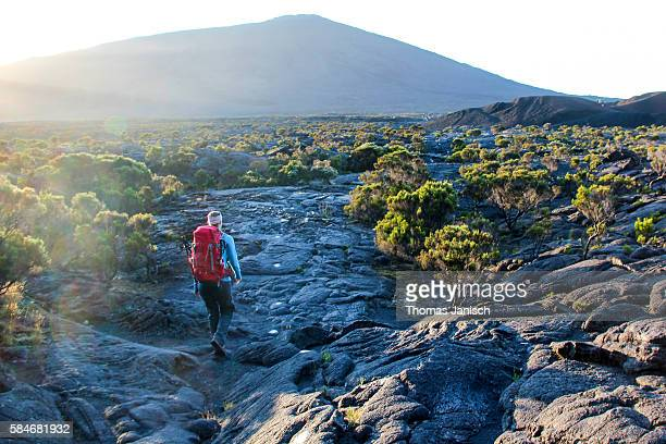 Hiking towards volcano Piton de La Fournaise during sunrise, Reunion island