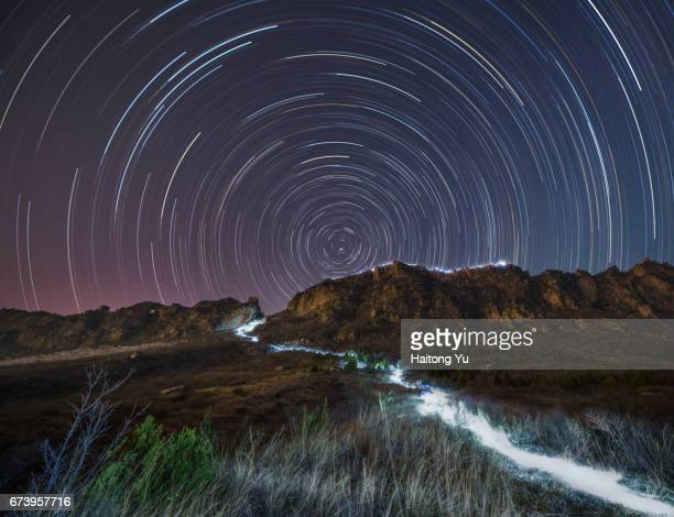 Hiking trail illuminated by headlight at night with star trails over the great wall on mountain ridge. Miyun, Beijing, China.