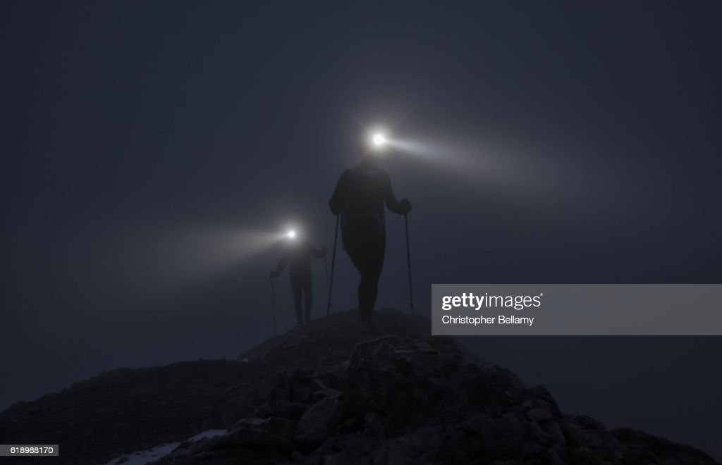 Hiking up ridge in darkness : Stockfoto