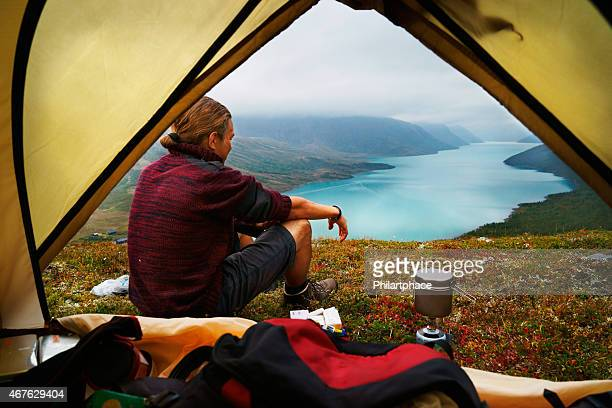 hiking young man and scenic view of lake gjende jotunheimen - camping stock photos and pictures