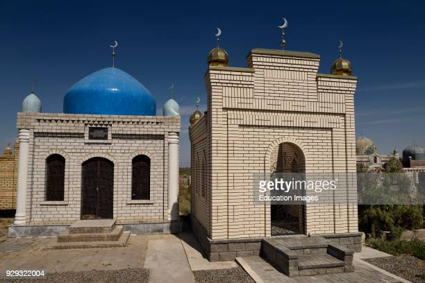 Hilal crescent moon symbols on Muslim brick mausoleums at a cemetery near Shelek Kazakhstan