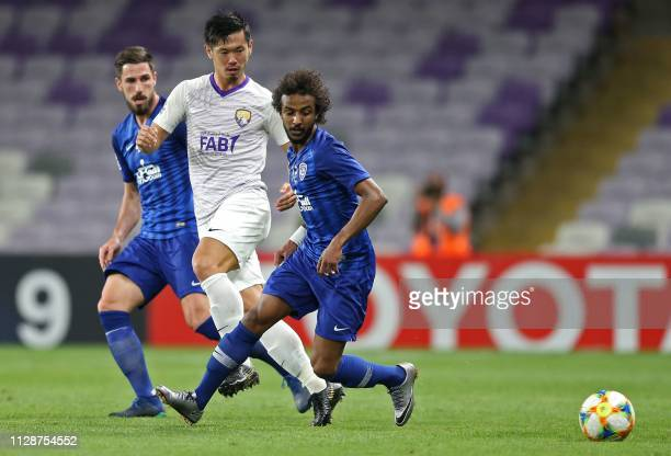 Hilal's defender Hassan Kadesh vies for the ball with Ain's defender Tsukasa Shiotani during the AFC champions league Group C football match between...