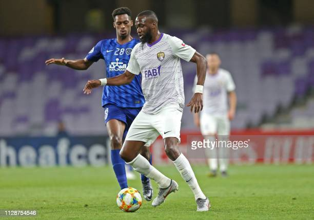 Hilal's midfielder Mohamed Kanno vies for the ball with Ain's midfielder Tongo Doumbia during the AFC champions league Group C football match between...