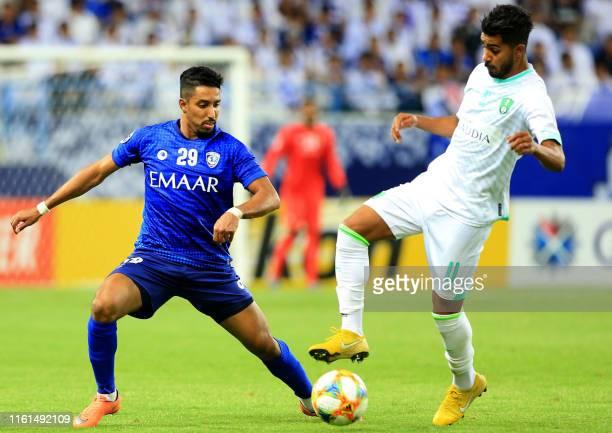 Hilal's Saudi midfielder Salem al-Dawsari vies for the ball against Ahli Saudi's Saudi midfielder Hussein al-Moqahwi during the AFC Champions League...