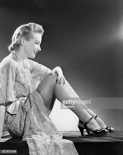 Hilarry Brooks sits on the floor with her legs tucked She wears a silk robe and high heels The robe is open to reveal the top of her thighhigh...