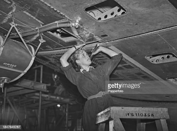 Hilary Bowman, an airplane examiner from the Aeronautical Inspection Directorate, Air Ministry, uses a torch to inspect the underside of the wing of...