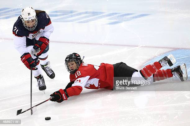 Hilary Knight of the United States and Catherine Ward of Canada go for a loose puck in the second period during the Women's Ice Hockey Preliminary...