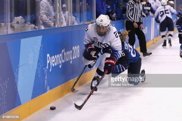 Hilary Knight of the United States battles for the puck against Sara Sakkinen of Finland in the first period during the Women's Ice Hockey...