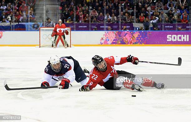 Hilary Knight of the United States crosschecks Hayley Wickenheiser of Canada during the Ice Hockey Women's Gold Medal Game on day 13 of the Sochi...