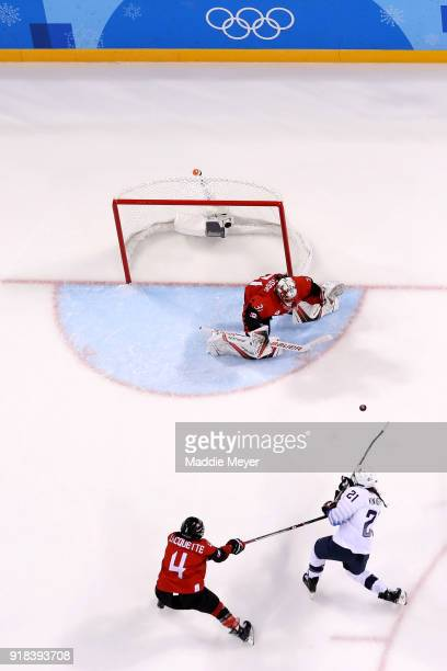 Hilary Knight of the United States shoots the puck against goalie Genevieve Lacasse of Canada during the Women's Ice Hockey Preliminary Round Group A...