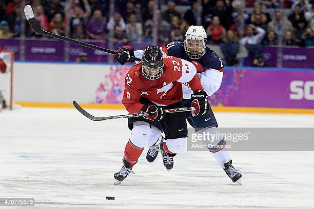 Hilary Knight of the USA gives pursuit to Hayley Wickenheiser of the Canada during the overtime period of Canada's 32 gold medal ice hockey win over...