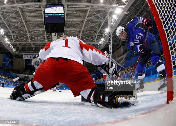 Hilary Knight right of the United States shoots against Russian athlete Valeria Tarakanova during the first period of the Women's Ice Hockey...