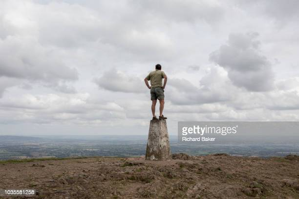 Hill climber stands on the top of the trig-point and looks across distant landscapes from the top of The Beacon, on 15th September 2018, in Malvern,...