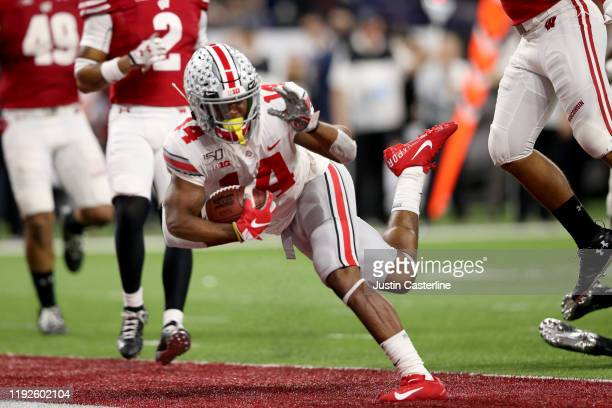 J Hill of the Ohio State Buckeyes runs the ball in for touchdown in the Big Ten Championship game against the Wisconsin Badgers during the third...