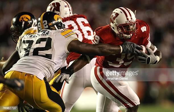 J Hill of the Wisconsin Badgers runs past the reach of Ken Iwebema of the Iowa Hawkeyes at Camp Randall Stadium September 22 2007 in Madison...