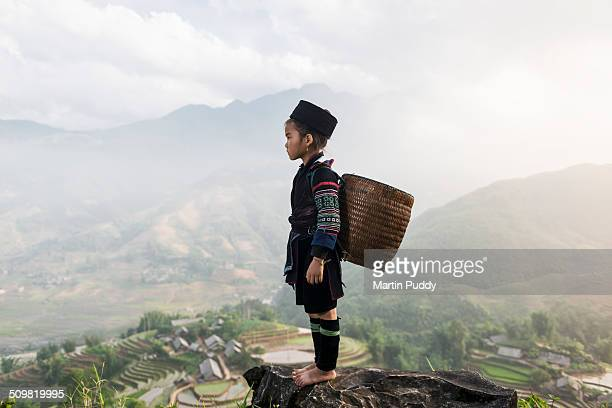 Hill tribe girl standing on hill side above valley