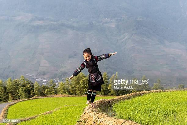 Hill tribe girl walking along rice paddy
