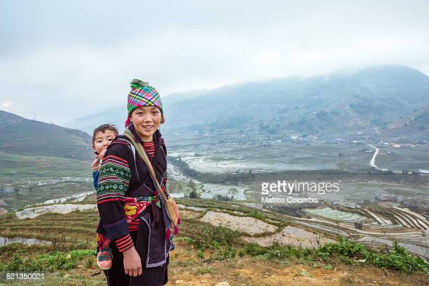 Hill tribe woman with baby in scenic landscape