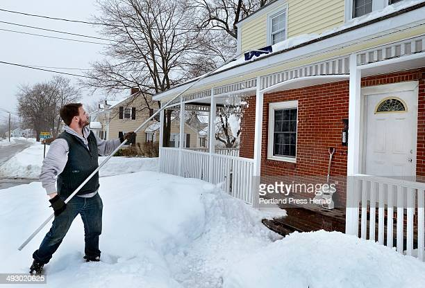 TJ Hill with Ram Island Home Grounds uses a snow rake to remove snow from the roof of a home in South Portland Friday February 21 2014