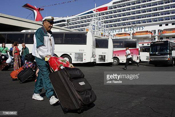Hillard Hicks walks with his luggage after disembarking from the Carnival Liberty Cruise ship at Port Everglades on November 19 2006 in Fort...