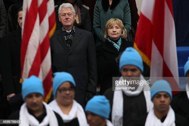 Hillary and Bill Clinton watch as New York City's 109th Mayor Bill de Blasio walks onto stage with his family at City Hall on January 1 2014 in New...